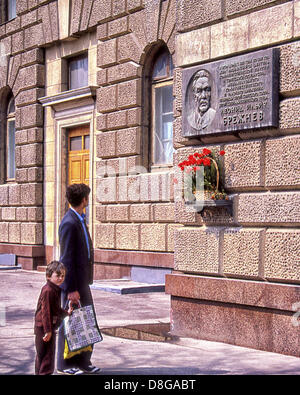 May 1, 1987 - Moscow, RU - A Russian man and young boy stop to view a commemorative plaque, and a shelf with flowers, - Stock Photo