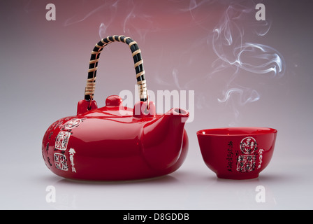 Chinese teapot with steaming cup - Stock Photo