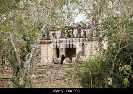 Female tourist in front of a small Mayan temple shrouded by jungle, Uxmal, Yucatan, Mexico - Stock Photo