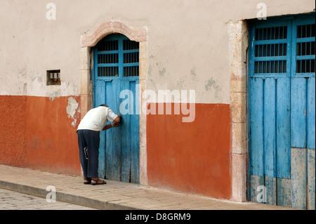 Man bending over to lock an old wooden door in Santa Elena, Yucatan, Mexico - Stock Photo