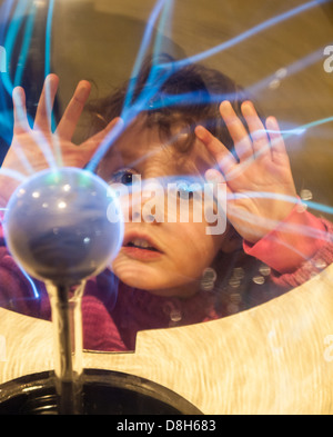 Small girl touches a plasma ball with her hands and watches the electrostatic discharge - Stock Photo