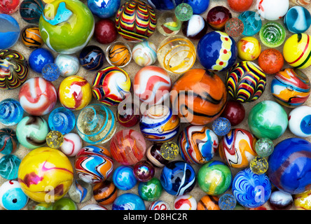 Colourful marbles on sand pattern - Stock Photo
