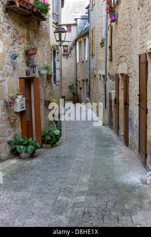 Doors and windows of medieval sandstone buildings along charming narrow cobblestone street in Sarlat, Dordogne region - Stock Photo