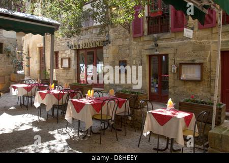 Sun-dappled outdoor courtyard restaurant among medieval sandstone buildings in charming Sarlat, Dordogne region of France