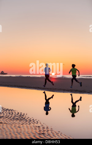 Two joggers running at beach - Stock Photo