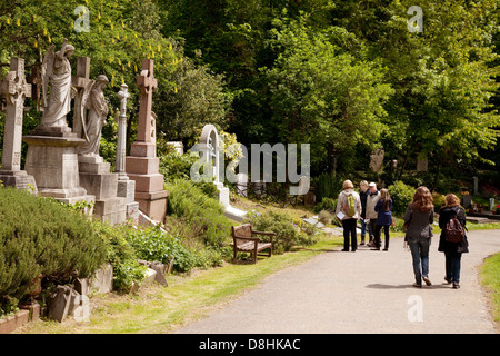 Visitors looking at the famous graves in Highgate cemetery East, London UK - Stock Photo