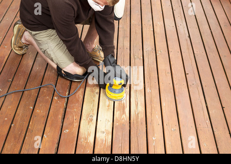 Horizontal photo of mature man kneeling while sanding outdoor wooden deck - Stock Photo