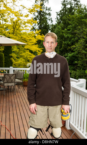 vertical photo of mature man preparing to sand outdoor wooden deck with patio furniture and trees in background - Stock Photo