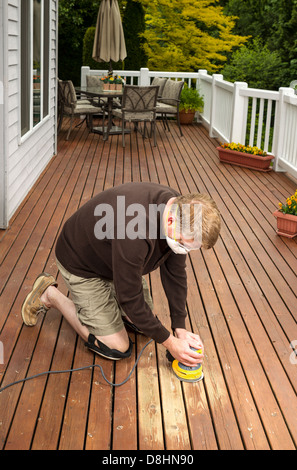 Vertical photo of mature man kneeling while sanding outdoor wooden cedar deck with patio furniture and trees in - Stock Photo
