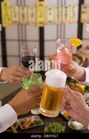 Four People Toasting with Each Other With Various Drinks at Izakaya - Stock Photo
