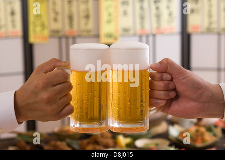 Two People Toasting with Beer at Izakaya - Stock Photo