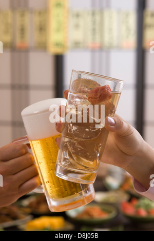 Two People Toasting with Beer and Chu-Hi at Izakaya - Stock Photo