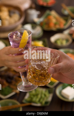 Two People Toasting with Whisky and Cocktail at Izakaya - Stock Photo