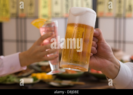 Two People Toasting with Beer and Cocktail at Izakaya - Stock Photo