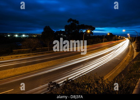 Light trails from cars sweeping past - Stock Photo