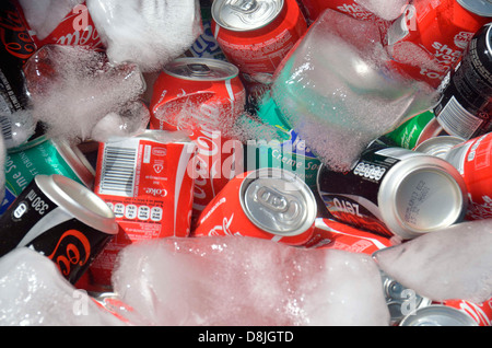 Tins of cold drinks or soda cans in ice water - Stock Photo