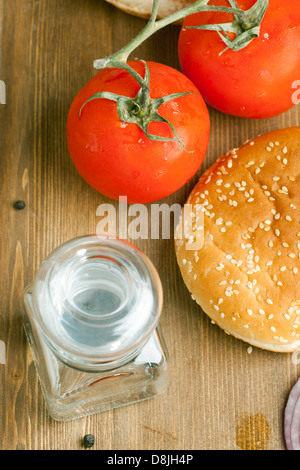 Top view on tow fresh tomatoes, burger's bun ad glass pot on wooden table - Stock Photo