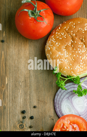 Top view on tow fresh tomatos, burger's bun and slised onion on wooden table as background - Stock Photo