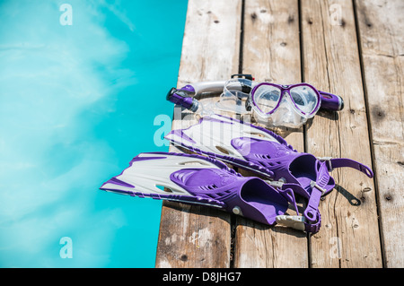 Diver eyeglasses, diving goggles, scuba snorkel and fins or flippers on the jetty (wood deck) near the water - Stock Photo
