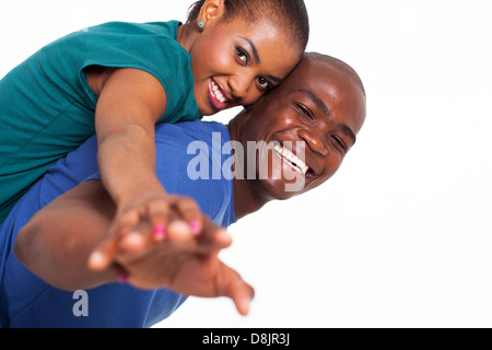 happy young african woman enjoying piggyback ride on boyfriends back with their hands outstretched - Stock Photo
