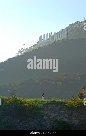 Woman standing at the foot of the hill with Hollywood sign, Los Angeles - Stock Photo