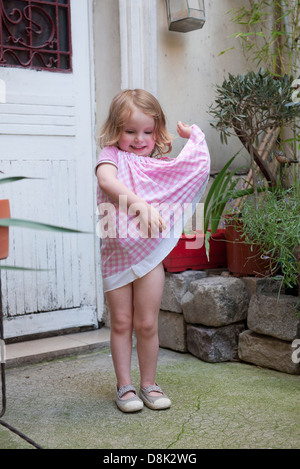 Little girl playing with dress, portrait - Stock Photo
