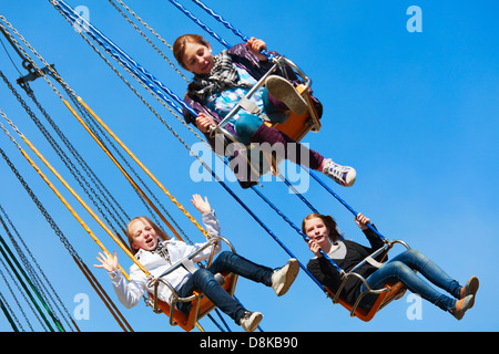 Teenage girls on the chain swing carousel - Stock Photo