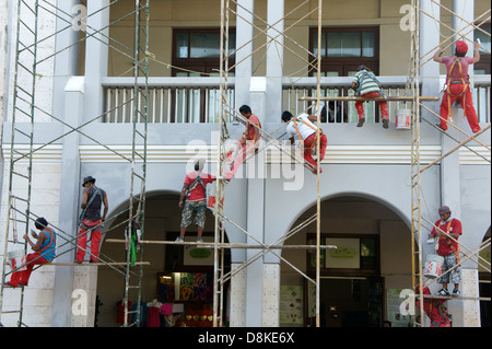 Workers on metal scaffolding painting the facade of a building in Merida, Yucatan, Mexico - Stock Photo