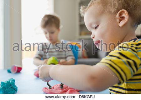 Boys playing with play dough at home - Stock Photo