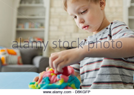 Boy playing with play dough - Stock Photo