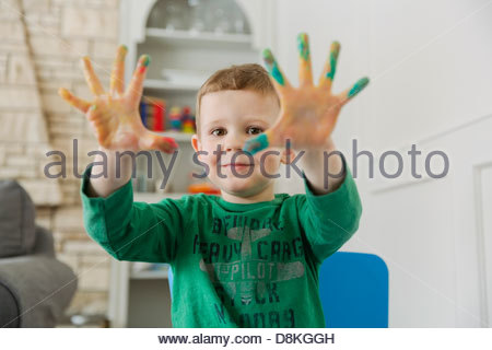 Portrait of boy finger painting at home - Stock Photo