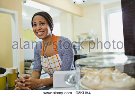 Smiling woman baker leaning on counter in bakery - Stock Photo