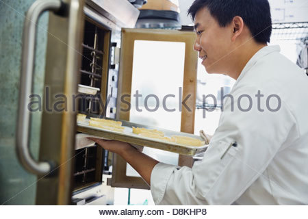 Male baker putting pastries in oven in bakery - Stock Photo