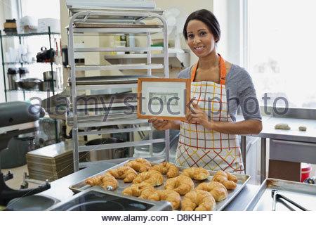 Portrait of woman baker standing in bakery - Stock Photo