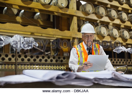 Male architect reading documents at construction site - Stock Photo