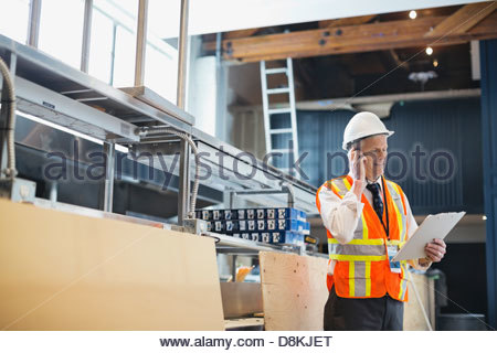 Male architect using mobile phone at construction site - Stock Photo