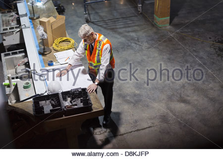 Male architect working on blueprint at construction site - Stock Photo
