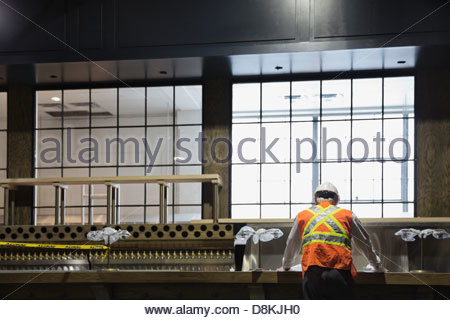 Rear view of male architect working at construction site - Stock Photo