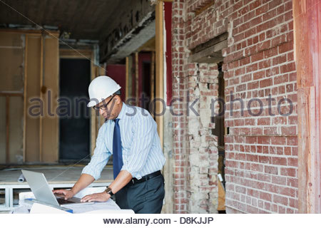 Male architect working on laptop at construction site - Stock Photo