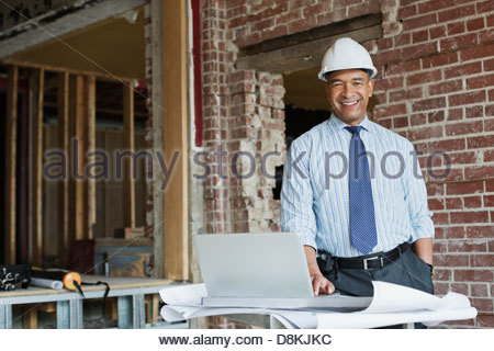 Portrait of male architect with laptop at construction site - Stock Photo