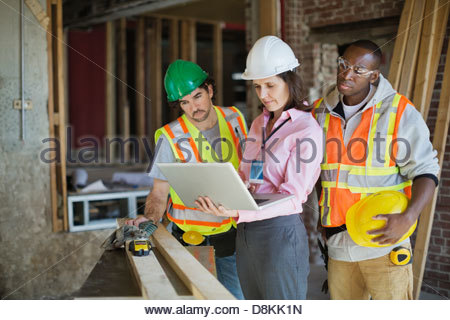 Female architect discussing plans on laptop with tradesmen at construction site - Stock Photo