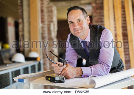 Portrait of male architect with blueprint at construction site - Stock Photo