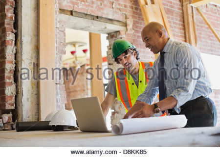 Male architect and tradesman discussing plan on laptop at construction site - Stock Photo