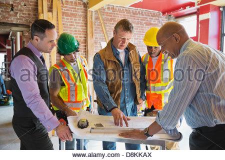 Foreman explaining blueprint to tradesmen at construction site - Stock Photo