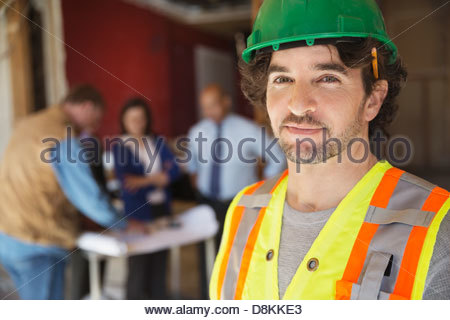 Portrait of tradesman with coworkers at construction site - Stock Photo