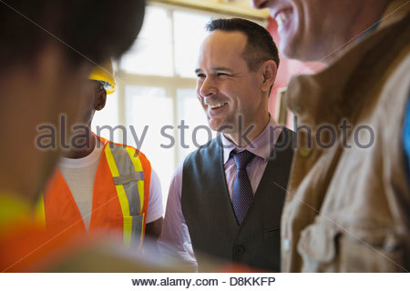 Smiling architect talking with team at construction site - Stock Photo