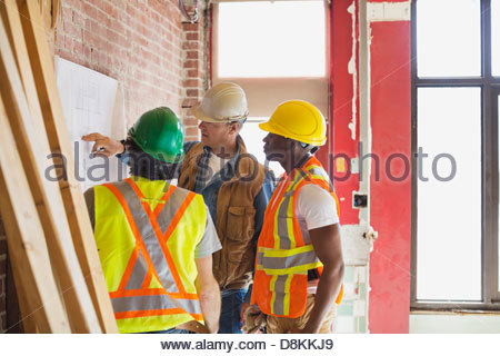 Foreman explaining blueprint to tradesmen at construction site - Stock Photo