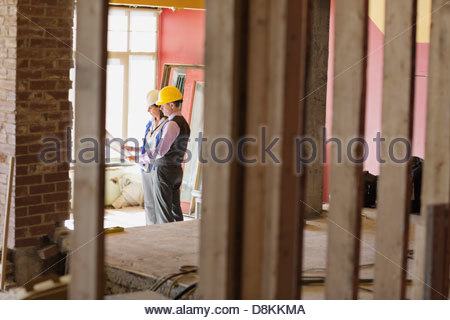 Male and female architects checking blueprint at construction site - Stock Photo