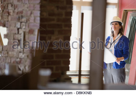 Female architect with blueprint at construction site - Stock Photo
