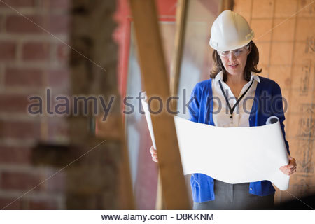 Female architect checking blueprint at construction site - Stock Photo